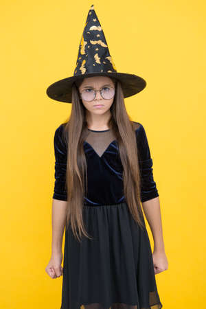 angry and unhappy kid wear witch hat and glasses ready for enchantment on halloween, happy halloween Stock Photo