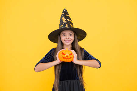 happy witch child with pumpkin jack o lantern wear costume of wizard on halloween party, halloween tradition