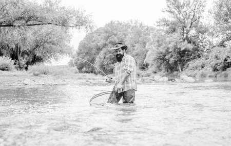 Bearded fisher catching trout fish with net. Fishing provides that connection with whole living world. Find peace of mind. Fishing is astonishing accessible recreational outdoor sport. Fishing hobby