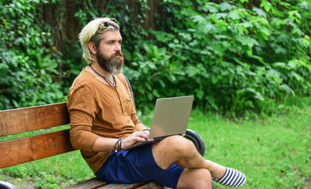 Homeschooling concept. online distant education. hipster inspired work in park. agile business. mature student working on computer. go shopping on cyber monday. bearded man sit on bench with laptop Standard-Bild