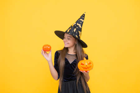 happy witch teenage girl with pumpkin jack o lantern wear costume of wizard on halloween party, halloween jack o lantern Stock Photo