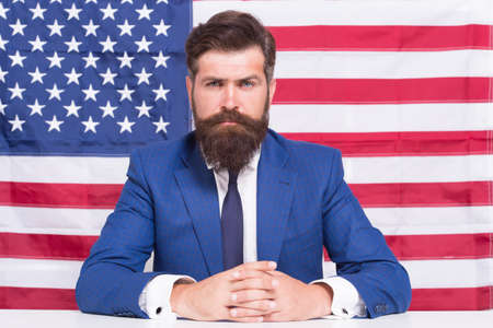 Man officiary placement working for american government USA flag background, serious situation concept Фото со стока