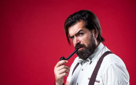 bearded man in suspenders smoke pipe. brutal guy wear bow tie. elegant male fashion look. handsome hipster in formal wear. party goer smoking. mature barber in retro style. copy space