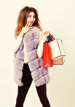 Shopping and gifts. Woman shopping luxury boutique. Lady hold shopping bags. Discount black friday. Fashionista buy clothes on black friday. Girl makeup furry violet vest shopping white background