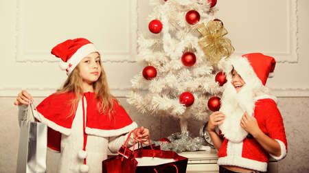 Kids celebrate christmas with gifts. Santa bring christmas gift. Unpacking christmas presents. Reason children love christmas. Boy kid santa with white artificial beard and red hat give bag to girl