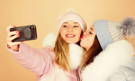 love you. happy winter holidays. Students friendship. girls in beanie. seasonal shopping. winter clothing fashion. down jacket. selfie time. women in padded warm coat. xmas vacation Archivio Fotografico