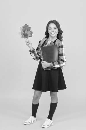 Learning foreign literature. Small child hold literature books and autumn leaves. Little girl go to English literature lesson. Childrens literature. School lesson. Education through reading Stock Photo