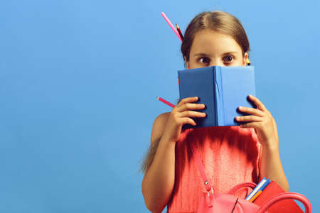 Girl with school bag hides behind blue notebook