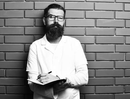 Bearded brutal caucasian doctor or postgraduate student with notebook Stock Photo