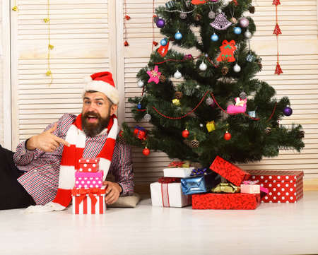 Man with beard points at present boxes. Celebration and gifts