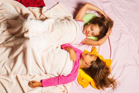 Schoolgirls have rest looking at each other. Kids in pajamas