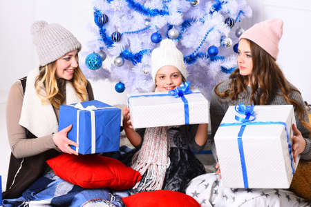 Girls with happy faces near white and blue Christmas tree Reklamní fotografie