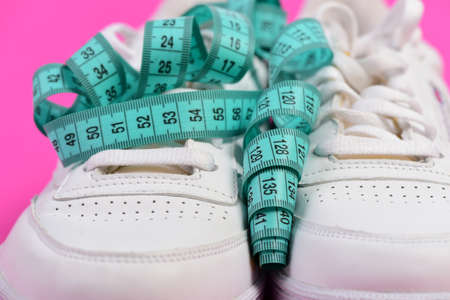 Morning run for health concept. Sneakers with measuring tape