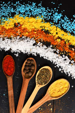 Food art. Composition of blue, white, orange and yellow salt.