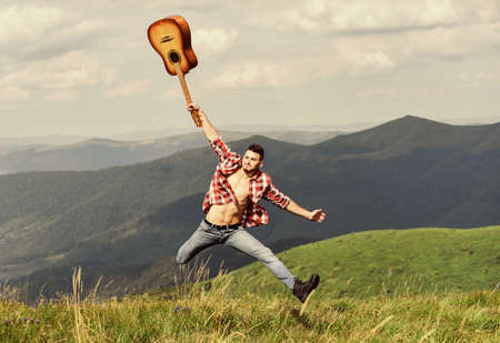 happiness. hipster fashion. western camping and hiking. happy and free. cowboy man with bare muscular torso. acoustic guitar player. country music song. sexy man with guitar in checkered shirt 스톡 콘텐츠