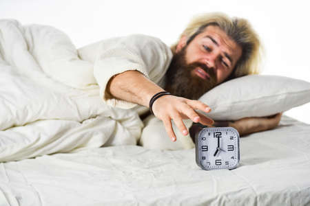 mature man turn off alarm clock. Digital alarm clock in bedroom. Time to wake up. Exhausted man being awakened by alarm clock in bedroom. Mature Man On Bed Turning Off Clock