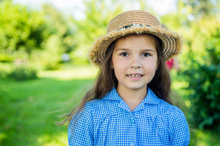Cute girl straw hat rustic style nature background, summer at countryside Reklamní fotografie