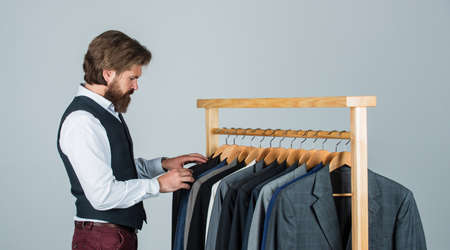 Every detail must be perfect. stylish business man at workspace. Fashion design studio. Male fashion designer. Individual measures hand of man. Man ordering business suit posing indoor
