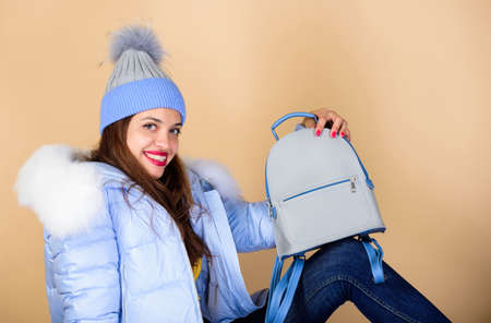 students life. girl in puffed coat. faux fur fashion. flu and cold season. Leather bag fashion. woman in beanie hat with backpack. warm winter clothing. shopping. happy winter holidays
