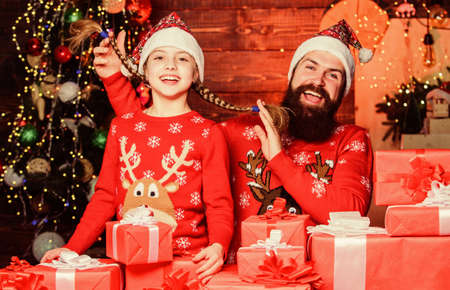 Come Santa Clause and dont delay. Father and child with gifts from Santa Claus. Father and daughter wearing Santa Claus hats. Happy family celebrate Christmas and new year. We believe in Santa Claus Reklamní fotografie