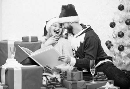 Celebrating new year together. Family tradition. Couple in love enjoy christmas. Happy flashback. Family cuddle near christmas tree while looking family photo album. Remember bright moments of year