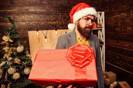 Spread happiness and joy. Bearded guy with eyeglasses carry present box. Delivery christmas present. Delivery service. Christmas is coming. Santa courier. Gifts delivery. Man santa hat deliver gift