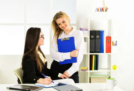 colleagues engaged in brainstorming talk chatting. explain ideas at workplace. business colleagues in modern office. coach speaking to assistant. women discuss work issues. Busy working day at work