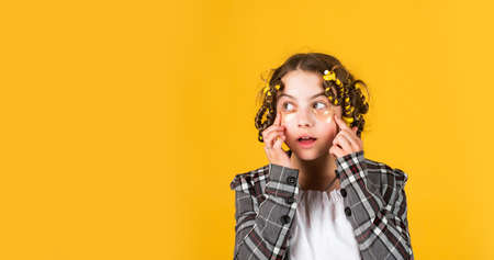 Hairdresser salon. Perfect beauty. Girl with curlers and hair clips in her hair on yellow background. Little girl curlers around her hair. Create beautiful hairstyle. Gorgeous hairstyle. Happy child