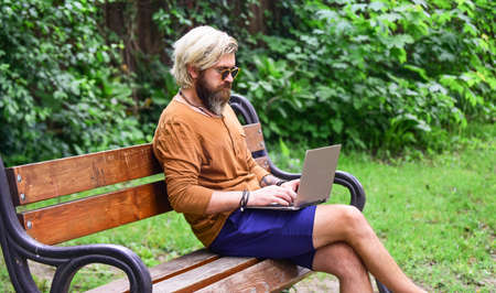 bearded man sit on bench with laptop. online distant education. hipster inspired to work in park. agile business. mature student working on computer. go shopping on cyber monday