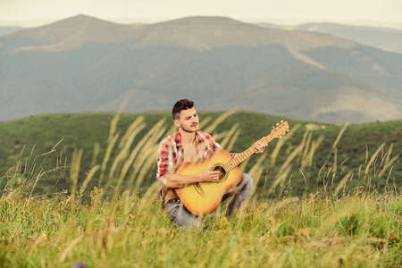 Classic Cool. acoustic guitar player. country music song. sexy man with guitar in checkered shirt. hipster fashion. western camping and hiking. happy and free. cowboy man play guitar outdoor 스톡 콘텐츠