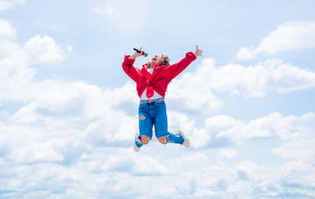 Happy kid with microphone. karaoke concept. Singing Songs. Lifestyle and People Concept. make your voice louder. teen girl singing song with microphone. having a party. jump so high Stockfoto