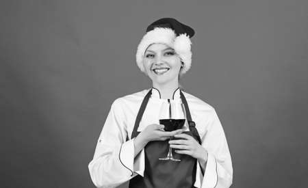 Enjoy easy ideas for holiday parties and holiday dinners. Festive menu concept. Christmas dinner ideas. Christmas menu. No stress. Woman chef cooking wear santa hat drink wine. Best christmas recipes Reklamní fotografie