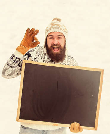 ok geture. happy hipster with blackboard. bearded man in warm clothes. Happy new year. winter season. Christmas sales. man advertising board. Copy space. winter holiday. Party here. ski and sledge