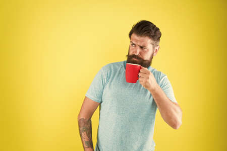 Morning habits lifestyle. Fanatic of coffee culture. Energy concept. Hipster barista yellow background. Coffee shop. Bearded man drink morning coffee. Tea time. Coffee with right proportion of milk