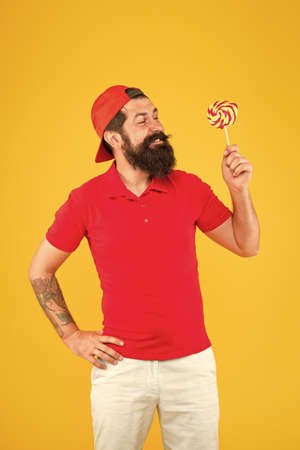 Nutritional values. Calories and vitamin. Homemade caramel candy. Sweets addicted. Hipster lollipop candy. Taste of childhood. Eating sweets. Man eat lollipop sweets. Having fun carefree man