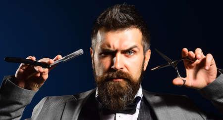 Man with beard holds shaving razor and scissors