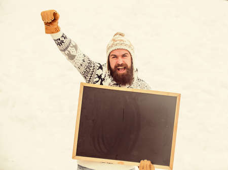 Winter event. Man with beard hold chalkboard copy space. Check it out. Winter holidays. Emotional guy snowy nature background. Winter announcement. Hipster knitted hat and gloves show blackboard