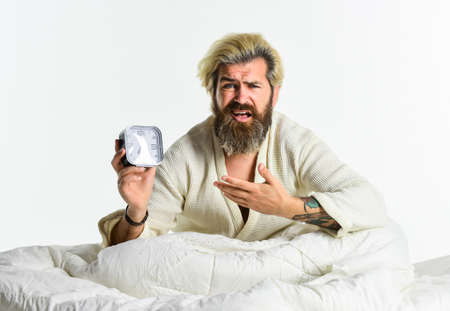 Sleep complex biological process that helps process new information, stay healthy and feel rested. Stressed man alarm clock. Sleepy guy and alarm clock in bed. Bearded man with alarm clock. Awakening