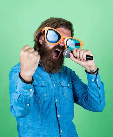 Modern music. hipster man with beard wearing glasses. music concept. have a happy holiday. have fun on party. male singer singing song in microphone. celebrate the anniversary. party goer Stock Photo