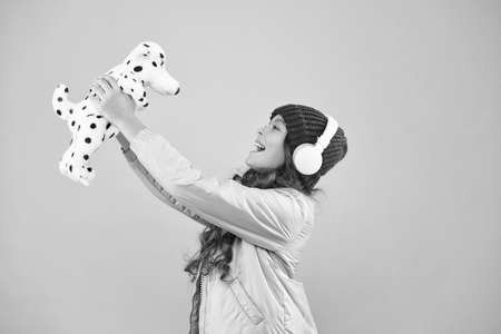 lets play together. pink is her favorite color. small kid listen music headphones. child long curly hair. cosy winter season. pet care. warm clothes for cold weather. happy little girl play dog toy