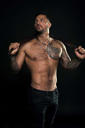 Punishment concept. Dominate male. Going to punish you. Fashion model with leather belt. Man with tattoo. Bearded man with muscular torso. Sportsman with tattooed arm and chest. Fitness and sport