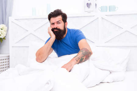 Lost in thoughts. brutal male does not feel rested. relax lifestyle concept. tired bearded man in bed. early wake up at morning. bachelor feel sleepy. guy at bedroom. lazy sunday. bed time routine