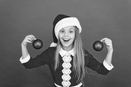 Create unique decorations. Christmas ball decor. Christmas decorating ideas for kids room. Child red costume hold christmas ornament. The earlier you shop for decorations, the cheaper they will be