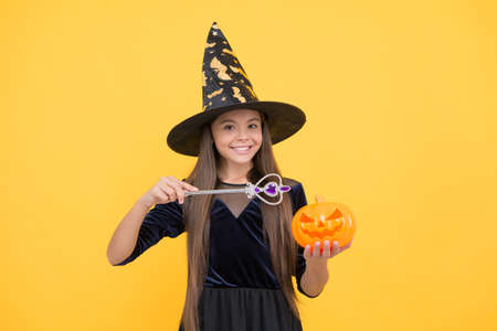 halloween kid in witch hat hold magic wand and pumpkin jack o lantern for witchcraft, halloween enchantment Stock Photo