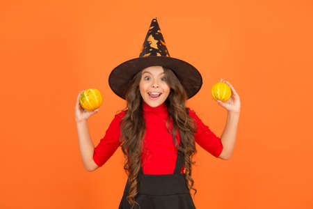 Happy childhood. autumn season holiday. childhood leisure. jack o lantern. happy halloween. kid wear witch hat. child with small pumpkin. girl has long curly hair and wear dress for party celebration