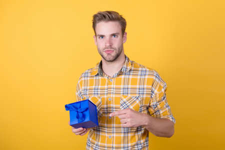 this is for you. present for holiday. trendy guy with bristle got surprise. black friday and cyber monday. handsome young man hold gift box. cheerful guy go shopping. friendly male shop assistant