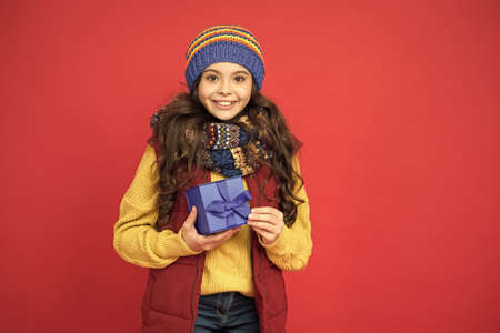 Pick some winter gifts for yourself. Wish list. Feeling grateful. Holidays season. Happy childhood. Christmas gifts and souvenirs. Winter holidays. Happy kid in winter outfit red background
