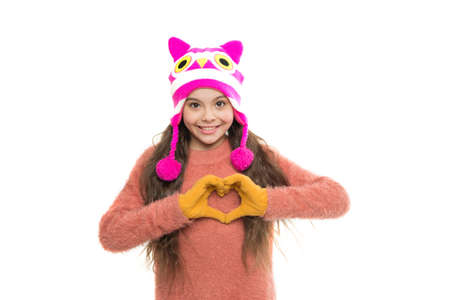 love in my heart. warm in any weather. let it snow. ski resort. get ready for winter holiday. homemade knit. little playful girl in winter look smiling. Fashion concept. cute beauty isolated on white