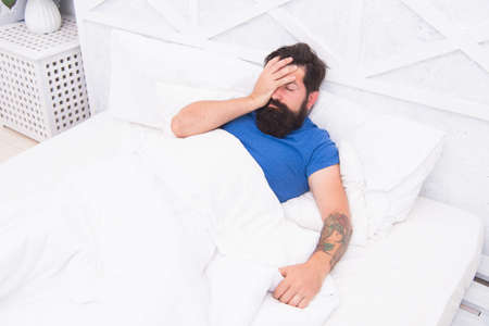 oh no. bachelor has hangover. guy at bedroom. lazy sunday. bed time routine. brutal male wake up with headache. relax lifestyle concept. tired bearded man in bed. early wake up at morning