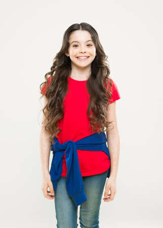 Hairdresser tip. Kid girl long healthy shiny hair. Perfect curls. Kid cute face with adorable curly hairstyle. Little girl grow long hair. Teen fashion model. Styling curly hair. Change you can see Stock fotó